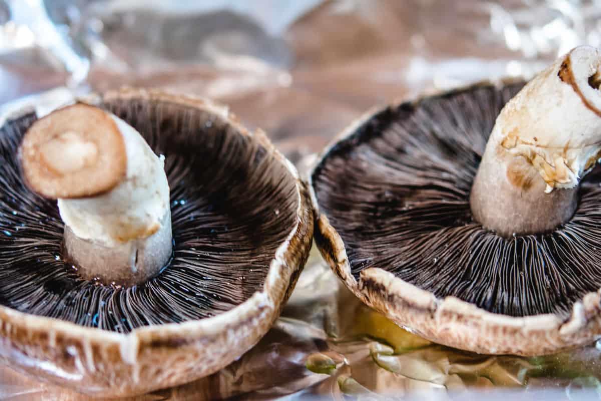 2 portbella mushrooms on a foil lined pan