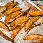 cooked potato wedges on a foil lined pan