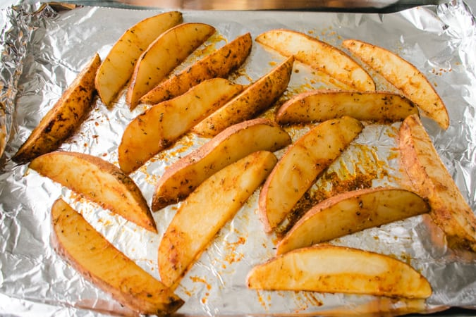 potato wedges spread onto a foil lined baking sheet