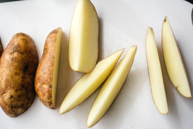 cut potato wedges on a white cutting board